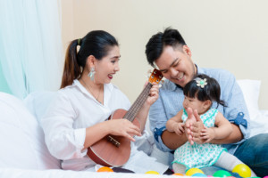 Young mother and father playing guitar and sing a song with little daughter in living room with happiness