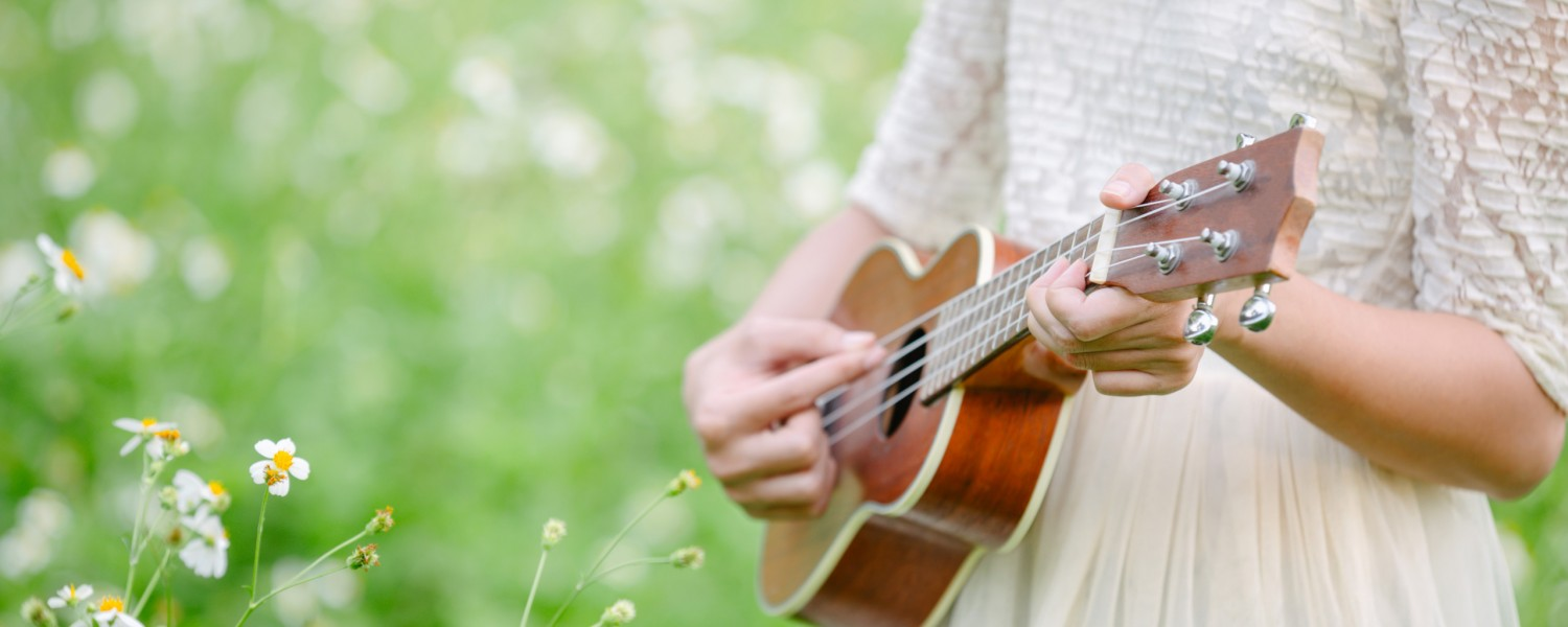 A beautiful woman wearing a cute white dress playing ukulele on a meadow with white flowers.